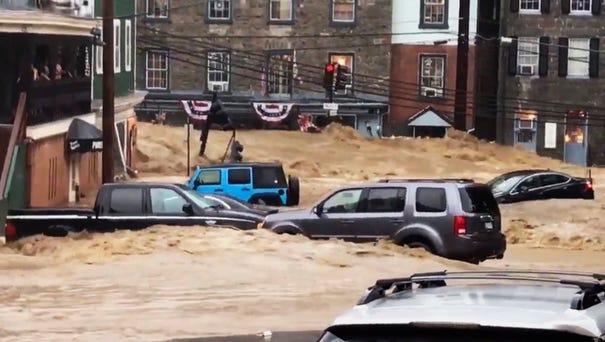 Water rushes through Main Street in Ellicott...