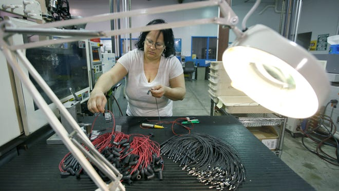 Machine operator Marisol Soto works on high voltage connectors ordered by Kodak at Custom Molding in Churchville, N.Y.