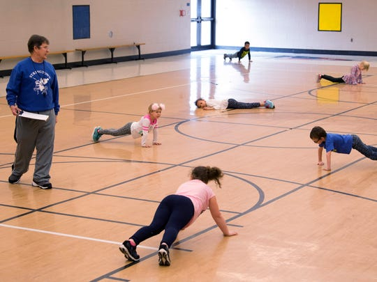 Physical Education teacher James Schmidt starts his first-grade charges with push-ups and other warm-up exercises at Stringtown Elementary School Thursday afternoon.