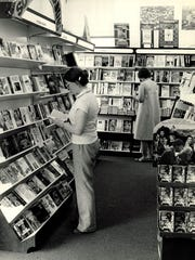 Village Green Bookstore employees Sarah Warren and Mary Sargent are seen in this 1980 photo looking through the many books stocked at the store.