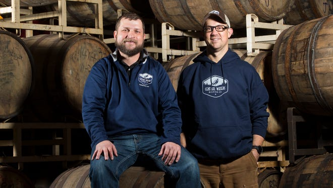 Central Waters Brewing co-owners Anello Mollica (left) and Paul Graham take a moment among the barrels in Amherst on Dec. 9, 2016.