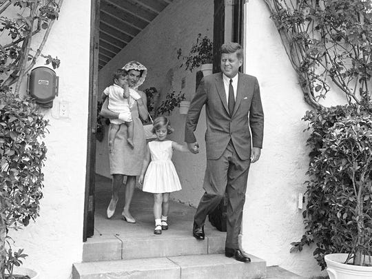 President John F. Kennedy and Jacqueline Kennedy leave their Palm Beach home to attend a private family mass April 22, 1962. Mrs. Kennedy carries John Jr., as the president holds Caroline by the hand.
