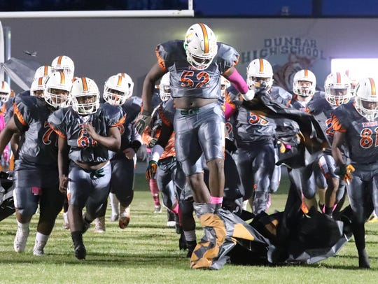 Dunbar's Derrick Hunter leads his team onto the field against North Fort Myers earlier this season.