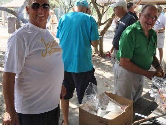 John Katulak (left) pauses from grill duty as Frank Scotti readies a hot dog bun at the Jupiter Senior Softball Association barbecue on Dec. 2.