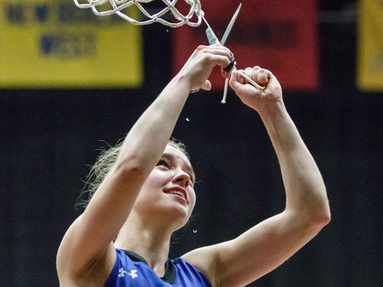 Senior Haley Zylka (1) cuts down a piece of the net after Oak Creek's 66-57 victory over Rufus King in the WIAA Division 1 sectional championship game at West Allis Central on Saturday, March 3.