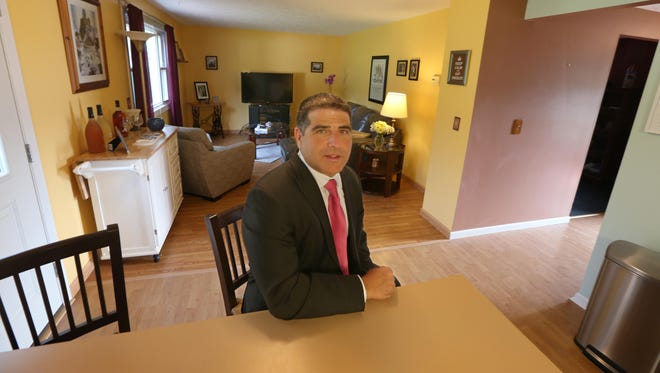 William Arieno, with Nothnagle Realtors, sits at kitchen counter with the living room behind him in a home he's listing in Henrietta.