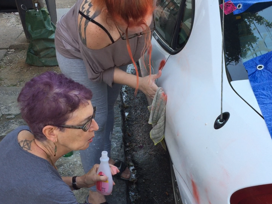 Nicole Hill and Nancy Josephson clean red paint off