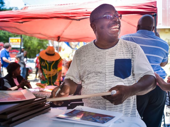 Mural Artist Adrian Fulton signing photos at the