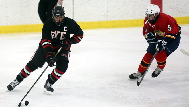 Pelham's Nate Rosenberg (5) tries to steal the puck away from Rye's Seamus Carroll (8) during ice hockey at the Ice Hutch in Mount Vernon Dec. 5, 2017. Dec. 4, 2017.