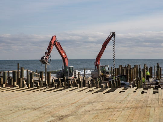 Workers dig the pilings as they work to  complete the