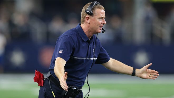 Dallas Cowboys head coach Jason Garrett congratulates his defense as they come off the field in the fourth quarter against the Tampa Bay Buccaneers at AT&T Stadium. Dallas beat Tampa 26-20.