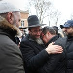 Mourners comfort each other after the killing of four French Jews in a kosher supermarket.