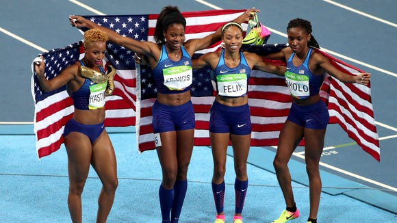Aug 20, 2016; Rio de Janeiro, Brazil; Natasha Hastings (USA), Phyllis Francis (USA), Allyson Felix (USA) and Courtney Okolo (USA) celebrate winning the women's 4 x 400m relay event during the Rio 2016 Summer Olympic Games at Estadio Olimpico Joao Havelange. Mandatory Credit: Erich Schlegel-USA TODAY Sports