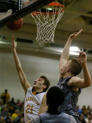 Clarkston's Tabin Throgmorton makes a layup past Dakota's John Hall, bottom and Thomas Kithier, top right, in the second half of the MHSAA boys regional finals basketball game on Wednesday, March 18, 2015 in Troy.