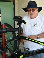 Bikes for Tykes founder Skip Riffle works on a bicycle to be donated.
