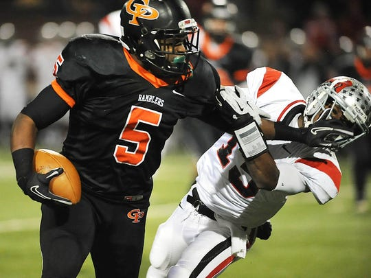 Erie Cathedral Prep's Delton Williams, left, stiff-arms West Allegheny's Donte McCallister on a carry in the second quarter of the PIAA Class AAA quarterfinal game at Veterans Stadium in Erie, Pa., on Nov. 30, 2012.