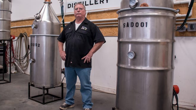 Scratch Ankle Distillery co-owner Bart Samaduroff stands Wednesday, Nov. 15, 2017, between two of the three stills his company uses to make small batches of whiskey, rum and moonshine at the business at 5930 Commerce Road in Milton.