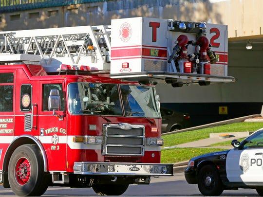 A Milwaukee fire truck and a Milwaukee police car.