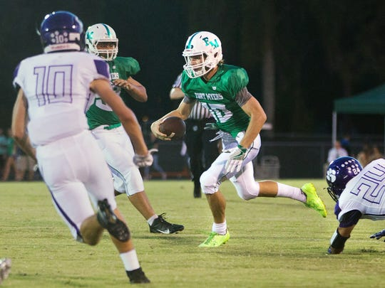Fort Myers High School's Ben Stobaugh picks up a first down against Cypress Lake during first quarter play Friday at Fort Myers High School.