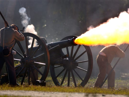 A Confederate cannon crew covers while firing a volley at oncoming Union troops during the annual Civil War re-enactment Raid in Fort Pierce. This is the 17th year for the re-enactment.