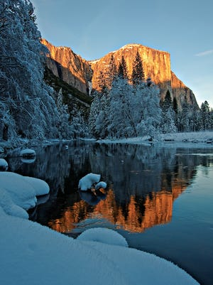 The face of El Capitan rises over snow-covered Yosemite National Park. In the summer months, the rock formation may be swarming with climbers; in the winter, it's stunning in its solitude.