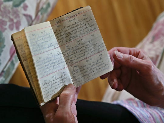 Sue Ellen Windsor looks over a diary and photo albums kept by her grandfather, J. Earl Windsor, during his time in Rochester during WWI when he was a student at the Aerial Photography School at Eastman Kodak, Tuesday, May 23, 2017, at her Penfield home.