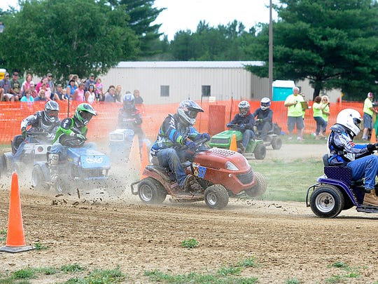 Lawn mower racers sped around a corner of the track kicking up dust and dirt Saturday during lawn mower races as part of the Grand Rapids Lions Club's annual music fest in Grand Rapids.