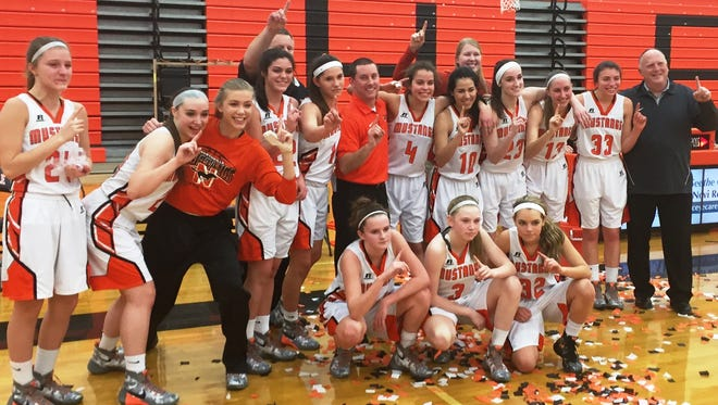 The Northville girls basketball team celebrates after clinching the KLAA Central Division title outright.