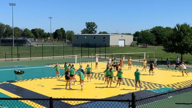 The Holland Christian volleyball team practices on a makeshift court on the tennis courts.