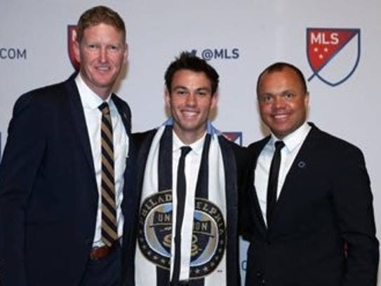 Taylor Washington, center, poses with Philadelphia Union head coach Jim Curtin, left, and sporting director Ernie Stewart after being selected in the 2016 MLS Superdraft. However, he only played 45 minutes in an exhibition match with the team, and was subsequently loaned to a lower-division team before Philadelphia opted not to renew his contract.