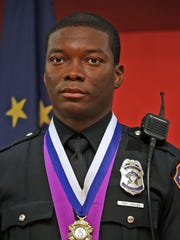 Indianapolis police officer Javed Richards stands at