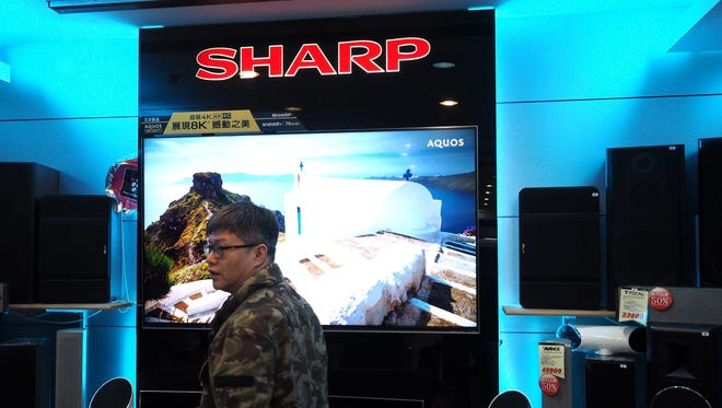 A picture made available on 25 Feb. 2016 shows a man walking past a SHARP TV screen at an electronics store in New Taipei City, Taiwan.