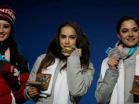 Medalists in the women's free figure skating, from right, Russian athlete Evgenia Medvedeva, silver, Russian athlete Alina Zagitova, gold, and Canada's Kaetlyn Osmond, bronze, pose during their medals ceremony at the 2018 Winter Olympics in Pyeongchang, South Korea, Friday, Feb. 23, 2018. (AP Photo/Charlie Riedel)