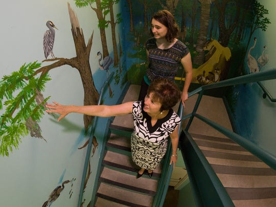 Commissioner Nancy Miller and Maia Hannahs admire the new stairwell mural.