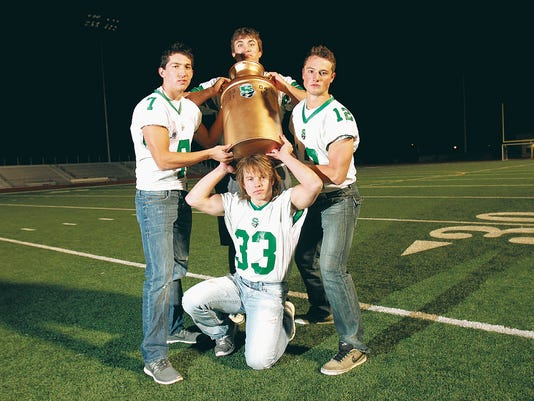 From clockwise top, Logan Welling (55), Jacob Lucas (12), Brian Farley (33) and Kyle Reynolds (7) hold up the milk can trophy on Wednesday at Hutchison Stadium in Farmington