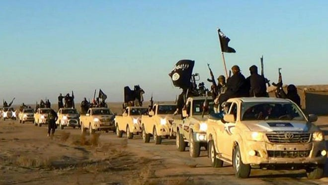 Militants of the Islamic State ride their vehicles in Raqqa, Syria.