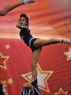 McClendon pulls an arabesque in her stunt while representing the Oklahoma Outlaws Cheer team in 2015. She cheered competitively on OOC for five years.