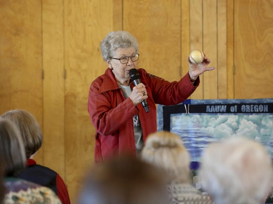"Lois Youngen, of Eugene, shows the 10 inch baseball that she used while addressing an audience at the Westminster Presbyterian Church in Eugene, Ore. on Jan. 13. Youngen was one of the 550 women who played professional baseball for 4 years after WWII. Their story was told in the film ""A League of Their Own."""