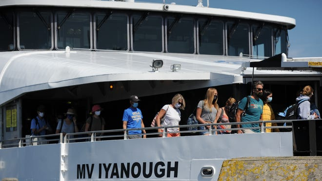 Masked ferry passengers debark the Steamship Authority's MV Iyanough after arriving on Nantucket Sunday afternoon. Nantucket and Martha's Vineyard have seen a noticeable increase in COVID-19 cases, prompting calls for more enforcement of restrictions to limit spread of the disease.