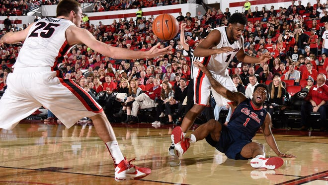 Guard Martavious Newby (1) loses the rebound to the defense of Georgia Bulldogs forward Yante Maten (1) and forward Kenny Paul Geno (25) during the first half at Stegeman Coliseum. The Rebels lost 80-66 to the Bulldogs on Saturday afternoon.