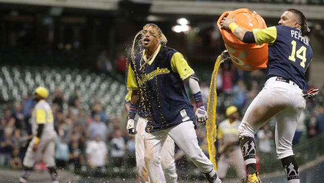 Milwaukee Brewers' Orlando Arcia celebrates after hitting a walk off single during the 15th inning of a baseball game against the Pittsburgh Pirates Saturday, Aug. 25, 2018, in Milwaukee. The Brewers won 7-6. (AP Photo/Morry Gash) ORG XMIT: WIMG124