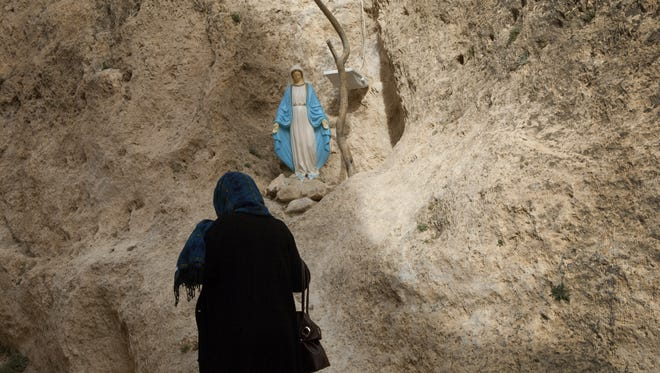 A Syrian woman prays at statue of the Virgin Mary in the rock gorge of Maaloula.