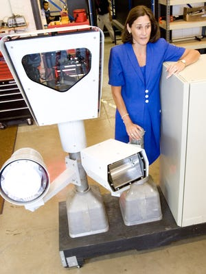 Karen Finley, the former CEO of Reflex, has pleaded guilty to a bribery and fraud scheme. She is seen here standing by a box containing apparatus used to capture photos of red-light runners.