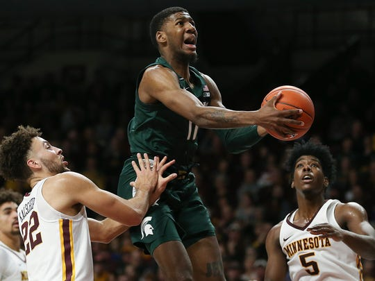 Michigan State's Aaron Henry, center, pushes up toward the basket against Minnesota's Gabe Kalscheur during an NCAA college basketball game Sunday, Jan. 26, 2020, in Minneapolis. (AP Photo/Stacy Bengs)