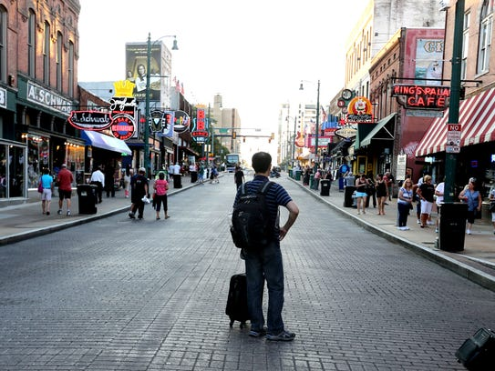 A tourist visits Beale Street in the Memphis downtown