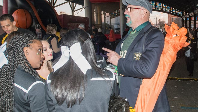 """Green-bearded """"Big"""" Al Neubert of Atlanta, a 1970 graduate of Ohio University, chats with Appalachian State cheerleaders. The Montgomery Advertiser Street Fest & Pep Rally for Camellia Bowl teams Appalachian State and Ohio was held on Friday, Dec. 18, 2015, under the Union Station Train Shed in downtown Montgomery, Ala. Activities included a pep rally for each team, live entertainment and interactive games for kids."""