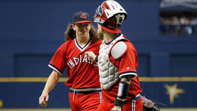 Cleveland Indians starting pitcher Mike Clevinger (52) smiles as he talks with catcher Roberto Perez (55) at the end of the third inning at Tropicana Field.