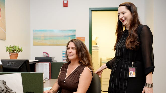 Reynolds High guidance counselor Laura McCreary looks over the shoulder of administrative assistant Stephanie Jones. The state General Assembly will consider giving schools more money to hire counselors like McCreary during its session that begins Wednesday.