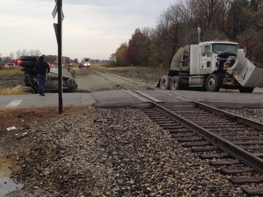 A semi-trailer split in two large pieces after an Amtrak