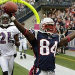 Then-New England Patriots wide receiver Deion Branch (84) celebrates a fourth-quarter touchdown as Baltimore Ravens cornerback Lardarius Webb (21) looks on during a 2010 NFL football game in Foxborough, Mass.